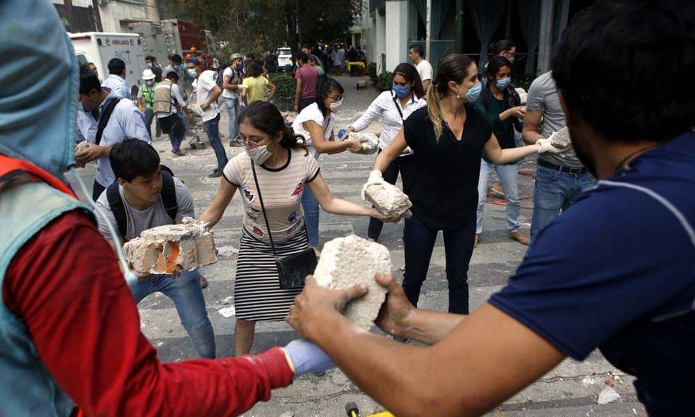 Cadenas humanas de civiles ayudando a quitar escombros después del sismo de la Ciudad de México